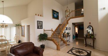 das Wohn-Esszimmer eines Duplex , weisser Marmorboden mit einem schwarzen Stern am Eingang, braunes Ledersofa und Treppen mit Holzveranda in den oberen Stock