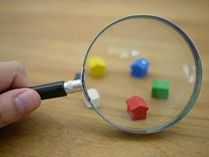 eine Hand die eine Lupe vor fünf Monopolihäuser hält, ein weisses, ein rotes, ein grünes, ein blaues und ein gelbes