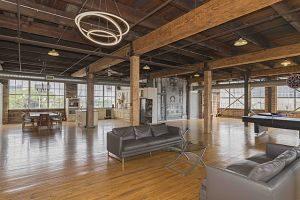 einzimmer-duplex mit Holzboden ins dachgeschoss mit vielen Fenstern und natürlichem licht, eingerichtet mit zwei schwarzen Ledersofas, ein Glastisch, eine tischtennisplate, weisse Einbauküche und Tisch mit Stühlen