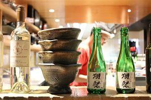 die eines asiatischen Restaurants mit einer leeren Flasche japanischen Weins , mehrere guseisenschüsseln und zwei leere Flaschen japanischem Biers