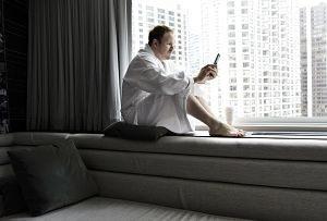 ein Mann in einem weissem Bademantel der auf der Fensterbank über einem grauem Sofa sitzt und aufs Handy schaut, die Sicht aus dem Fenster sind Hochhäuser