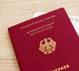 ein roter Reisepass der europäischen union auf einem hellem Holztisch