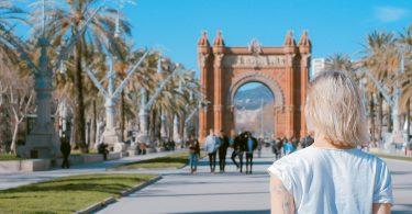 Die Allee zum Triumph Tor in Barcelona, es ist eine junge blonde Frau mit weisem T-shirt von hinten zu sehen, die auf einem Arm eine geometrische Figur und auf dem anderen Blumenzweige tätowiert hat