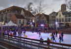 eine Schlittschuhbahn auf einem Marktplatz mit vielen Leuten darauf, Kinder mit Fahrhilfen und weihnachtslichter über der Bahn und in den bäumen