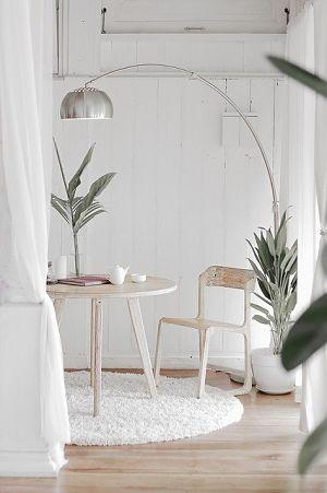 teil eines Zimmer mit weissen Wänden und Vorhängen, in der Ecke steht ein Tisch und ein Stuhl aus Holz, eine moderne Stehlampe zwei Pflanzen aus der Familie der Palmen und auf dem Tisch eine kleine weisse Teekanne und eine kleine weisse Tasse