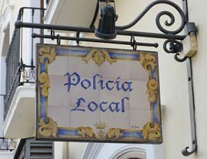 antikes Straßenschild aus Porzellan in blau eins und gelb mit der Aufschrift Bolivia local und dem Wappen der Lokalpolizei