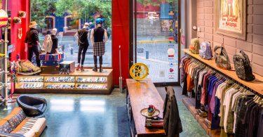 Innenraum eines tranigem modernen laden, rechts sind t-shirts, Jacken und Hemden aufgehängt am Eingang steht ein länglicher Holztisch, im Schaufenster vier Mannequin auf einem Regal in dem Schuhe eingeordnet sind und über den t-scirts verschiedenen Rucksäcke
