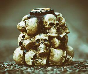 eine art Talisman bestehend aus zirka achtzehn kleinen Totenköpfen die um einen kurzen Holzstab geklebt sind