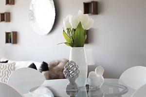 ein inszeniertes Wohnzimmer mit weissen Tulpen auf einem Glastisch und einer kuscheligen Decke auf weisem Sofa mit Kissen in Brauntönen