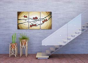Backsteinboden und graue Wand, eine Holztreppe mit Glasschutz davor, zwei grüne Planzen vor dem aufstieg der Treppen und an der wand hängt ein dreiteiliges bild mit ästen und roten Vögeln darauf
