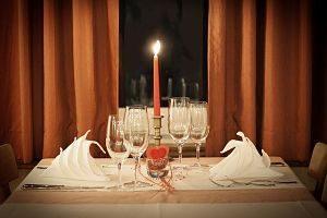 ein Tisch gedeckt für zwei Personen mit einer angezündeten roten Kerze und einem rotem Herz in der Mitte als Dekoration, dahinter ein Fenster, es ist dunkel und dunkel orangene Vorhänge