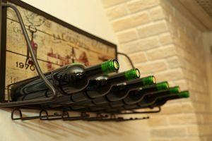 ein sehr altes Weinregal aus Eisen auf dem drei unetiquetierte grüne volle Weinflaschen liegen