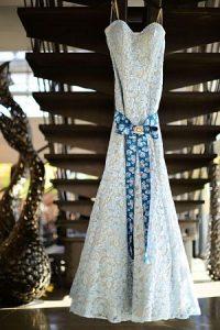 ein weisses Blumenkleid mit einem blauem langen Band das vorne als schleife lange runterhängt und unter einer Treppe hängt