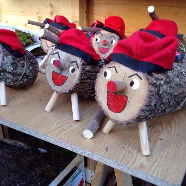 auf einem Holzbrett sind verschieden große cagatios aufgestellt, alle mit rotem offenem Mund und der traditionellen roten Mütze mit schwarzen Streifen