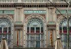 Der Eingang der Teatre del Liceu in Barcelona, beige Fassade mit hellgrünen Details und einer spanischen Flagge links und einer katalanischen Flagge rechts von der Tür