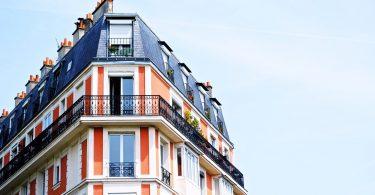 ein Apartment Hochhaus in rot und weiss gestrichen mit einem dunkelgrauem Dach, das vorletzte Stockwerk hat einen Balkon um das ganze Gebäude