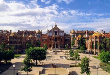 Vorderansicht der modernistischen Anlage des Krankenhauses San Pau in Barcelona, Gebäude in roten färben und ein kleiner Park davor