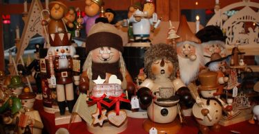 Stand eines Weihnachtsmarkts auf dem verschiedenen handgemachte Holzfiguren ausgestellt sind