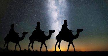 in der Wüste sind drei Kamele mit drei Männern zu sehen wie sie durch die nacht ziehen, vermutlich die heiligen drei Könige