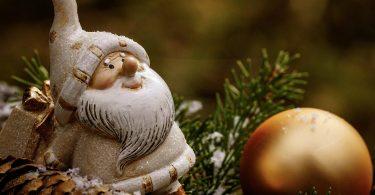 ein weissgekleideter Nikolaus auf einem Tannenzwei, daneben ein länglicher Tannenzapfen und vor ihm liegt eine goldenen Kugel