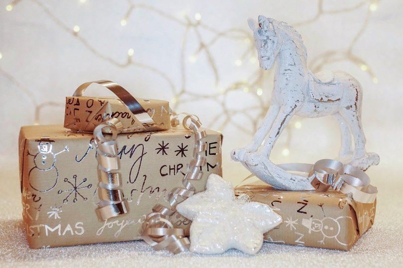 drei Geschenke in braunem Geschenkpapier mit silberner Schrift, Schneeflocken und Schneemännern, mit einem silbernem Band, einem kleinem weissen Schaukelpferd und im Hintergrund eine Lichterkette