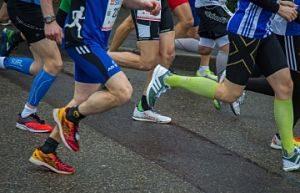 mehrere Renner auf einer Straße, einer mit blauem T-shirt und kurzer Hose,, und orangenen Turnschuhen und daneben einer in schwarzer kurzer Hose mit grünen Turnschuhen und grünen Kniestrümpfen