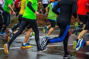 eine nasse Straße und mehrere Marathonläufer in Turnschuhen und Loggins und kurzen Hosen