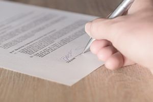 zu sehen ist ein Blatt eines deutschen Mietvertrags der gerade von jemandem mit einem silber färbenden und blauschreibenden Kugelschreiber unterzeichnet wird