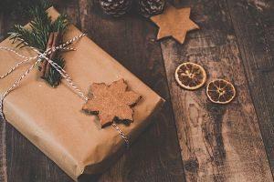ein in braunem Papier eingepacktes Geschenk mit einem rot-weisem Faden drum herum zwei sternförmige Kekse und zwei getrocknete Orangenscheiben