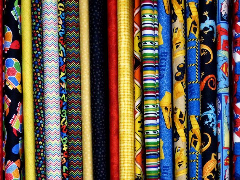 aufgerollte Stoffe in verschiedensten Farben und Mustern die nebeneinander aufgeregt sind