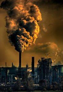 ein großes Fabrikgelände bei Dämmerung das enorme Mengen an Dampf ausstössst