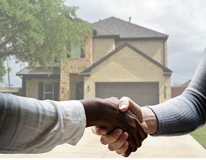 zwei Männer die sich vor einem Haus die Hände schütteln, einer mit weissem Hemd der andere mit grauem Pullover