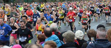 Eine breite Alles voller rennender Leute die an einem Marathon teilnehmen, der Boden ist nass aber es regnet nicht