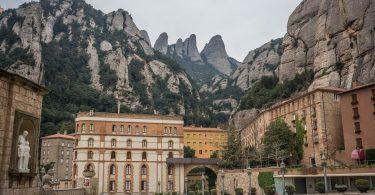 im Hintergrund das Felsengebirge von Montserrat und im Vordergrund Hausblöcke in rot und orange Tönen