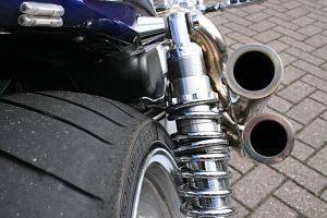 zu sehen ist ein Auspuff eines blauen Motorrads und Teil des Hinterreifens
