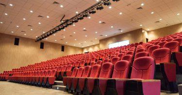 ein leerer beleuchteter Kinosaal mit roten Sesseln und Beigem Teppichboden