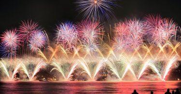 Feuerwerk am Hafen, unten sieht man helle Feuerwerksfontainen, darüber fünf runde Feuerwerke in lila und ganz oben wie ein lila Stern, im Vordergrund die Schatten vereinzelter Personen