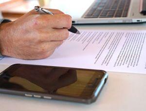 ein einem Immobilienbüro geht ein angestellter gerade einen Vertrag durch, zu sehen ist seine Hand mit einem Kugelschreiber , der Vertrag, links davon ein schwarzes Handy und rechts davon ein Laptop