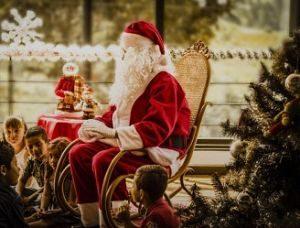 Der Weihnachtsmann auf einem Schaukelstuhl neben einem Christbaum und um ihn herum sitzen viele Kinder die in gespannt ansehen und zuhören was er sagt