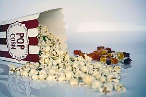 eine umgefallene Popcorntüte aus der das Popcorn rausgefallen ist und daneben eine Handvoll Gummibären in verschiedenen Farben