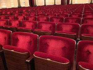 mehrere aufklappbare Sessel eines Theaters die mit einem rotem Samtstoff bezogen sind