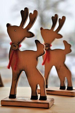 zwei Rentiere aus Holz die nebeneinander auf einem Tisch stehen, sie tragen um den Hals einen roten Faden mit einem kleinem Holzknopf und strecken ihre Nasen in die höhe