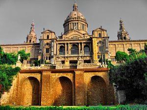 das nationale Kunstmuseum von Barcelona, man sieht von vorne das ganze Gebäude mit der Kuppel in der Mitte und zwei türmen links und rechts, davor grüne Wiese und einige Blätterbäume