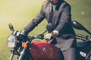 ein Mann mit Bart und grauem Anzug der auf einem rotem Motorrad sitzt und beide Hände am Lenkrad hat, hellgrüner verschwommener Hintergrund