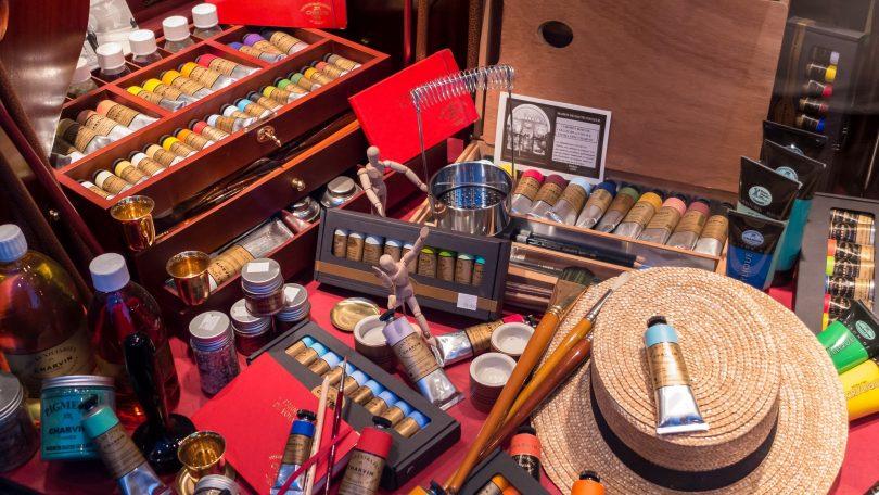 ein Schaufenster eines Bastelgeschäfts mit verschiedenen Farbtuben, Pinseln, Holzigsten mit Farben, ein Strohhut und kleine menschliche Holzfiguren