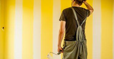 ein Mann in grauer Latzhose der ein der linken Hand einen Wandroller hält und sich mit der rechten Hand am Kopf kratzt, er steht vor einer gelb weiss gestreiften Wand in einer Wohnung
