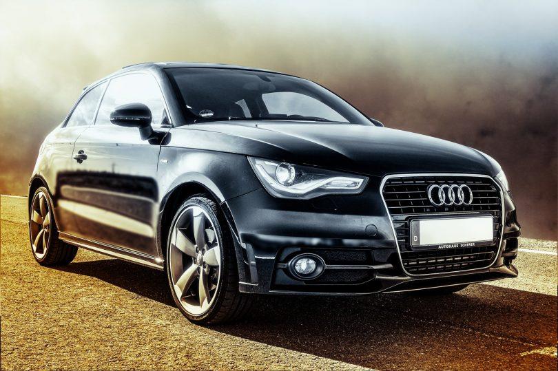 ein schwarzer Audi mit weissem Kennzeichen der auf einer Straße steht