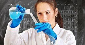 eine junge Frau in weisser Jacke die blaue Gummihandschuhe trägt und eine hellblaue Flüssigkeit von einem Reagenzglas in ein anderes füllt, dahinter ist eine Tafel mit den chemischen Elementen zu sehen