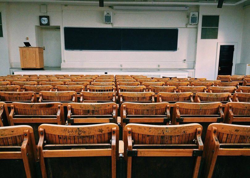 ein leeres Klassenzimmer einer Universität, ganz vorne eine lange Tafel und ein Lehrerpult und der erst des Raumes ist mit klappbaren Holzstühlen und Tischen gefüllt