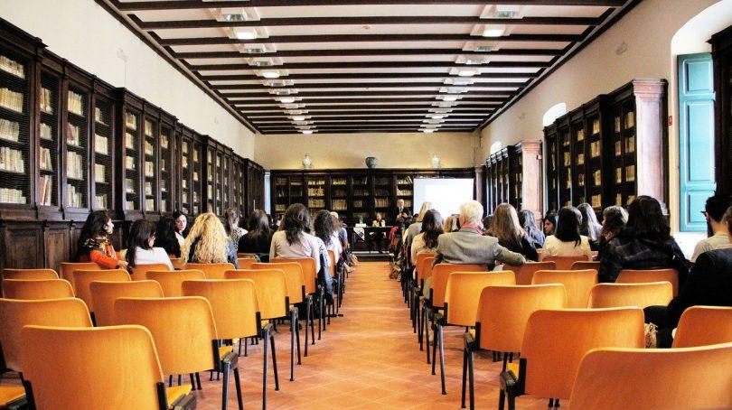 Versammlung in einem länglichen Sal mit Bücherregalen an allen Wänden, bis auf einen Gang in der Mitte steht alles voller orangener Stühle, von denen nur die Hälfte von Personen besetzt sind und am Ende der Raumes ein Tisch en dem drei Personen sitzen